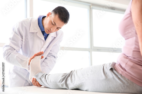 Fotografia  Physiotherapist working with mature patient in rehabilitation center