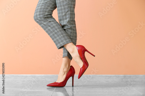 Obraz na plátně  Young woman in high-heeled shoes against color wall