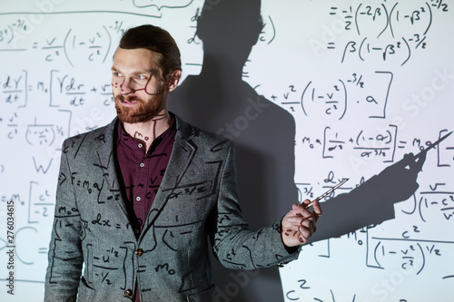 Photo Content confident young bearded math teacher in jacket standing against projecti