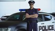 Brave policeman in service cap and sunglasses posing for camera near patrol car