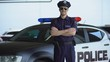 Handsome police officer smiling, standing near new patrol car, law and order
