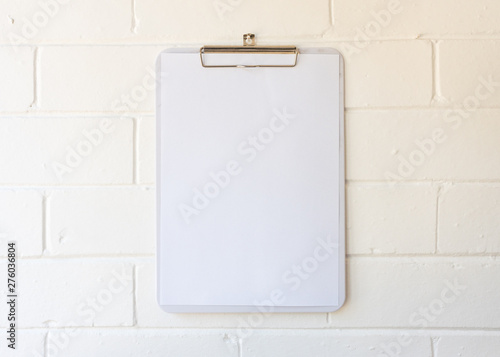 Fotografía  Close up of blank A4 page on clipboard hanging against white painted brick wall