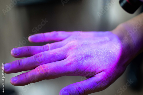 Valokuva  Hands under black UV light to detect glow in the dark germs around nails and fin