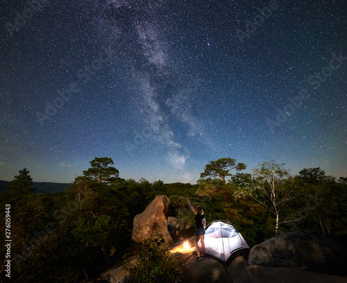 Fototapeta Rear view of woman hiker resting on rocky mountain top beside camp, campfire and tourist tent at summer night, pointing at sky full of stars and Milky way. On background starry sky, boulders and trees obraz na płótnie