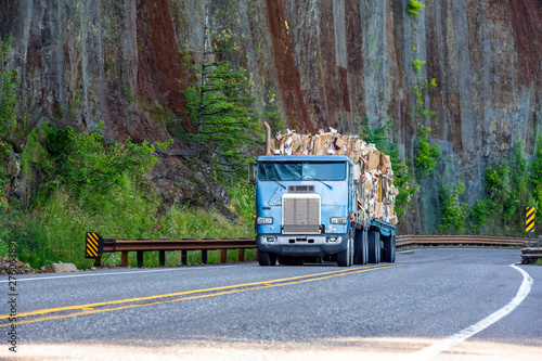 Old big rig cab-over semi truck transporting paper recycling on flat bed semi trailer driving on mountain winding road with rock wall