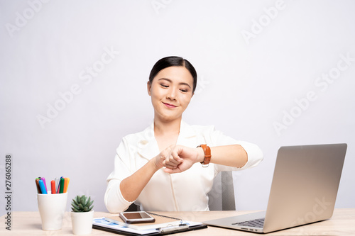 Fotografia, Obraz Happy woman holding hand with wrist watch at office isolated over background