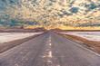 asphalt road with cloudy sky above Lut desert,hottest desert in the world, also known like Kalut Desert