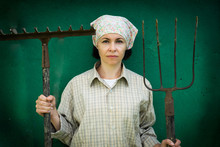 Young Woman Stands With A Pitchfork Near A Stable On A Ranch.
