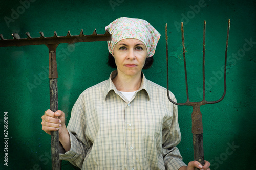 Obraz na plátne Young woman stands with a pitchfork near a stable on a ranch.