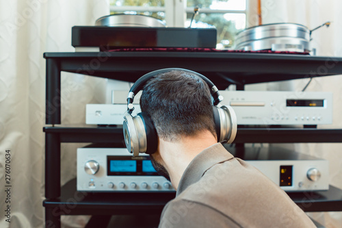Man turning up the volume on home Hi-Fi stereo Canvas Print