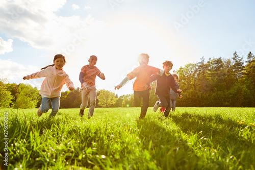 Foto op Canvas Op straat Kinder laufen und spielen auf einer Wiese
