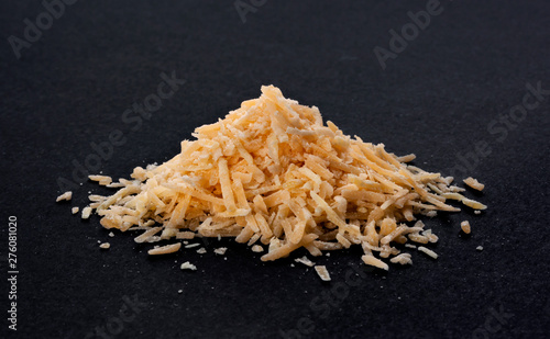 Obraz na płótnie Pile of grated cheese on black background