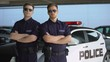 Confident male officers in sunglasses standing against police car background