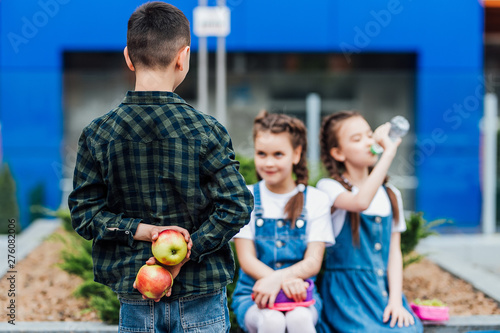 Focus at boy holding two apple in hands for his girlfriends in school Wallpaper Mural