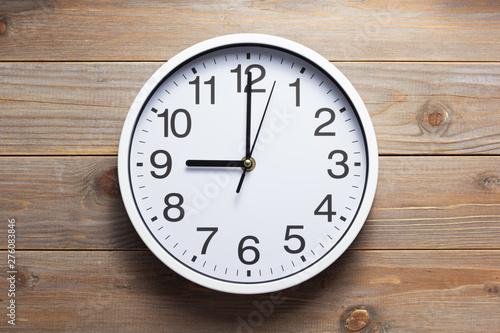 Fotografia  wall clock at wooden background