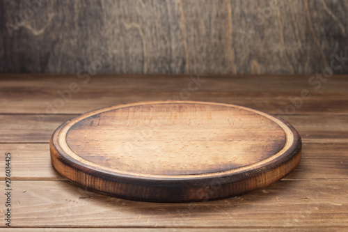 Obraz pizza cutting board at rustic wooden table in front - fototapety do salonu
