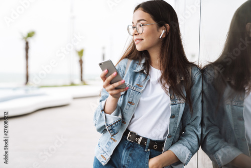 Fotografia  Smiling young pretty woman student wearing eyeglasses walking outdoors listening music with earphones using mobile phone chatting