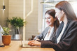 Two Asian businesswoman in suit happy working with laptop at modern office