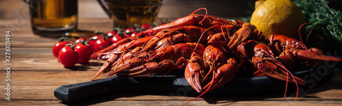 Photo  panoramic shot of red lobsters, tomatoes, dill, lemon and glasses with beer on w