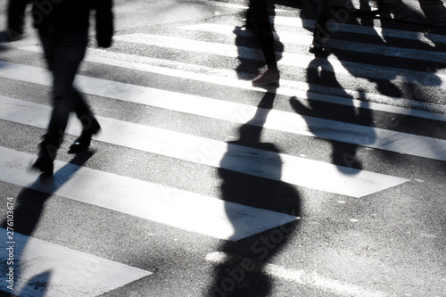 Fotografiet Blurry zebra crossing with pedestrians making long shadows