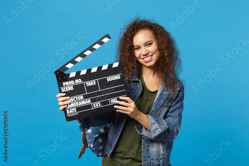 Obraz na plátne Young african american girl teen student in denim clothes, backpack hold clapper isolated on blue background studio portrait