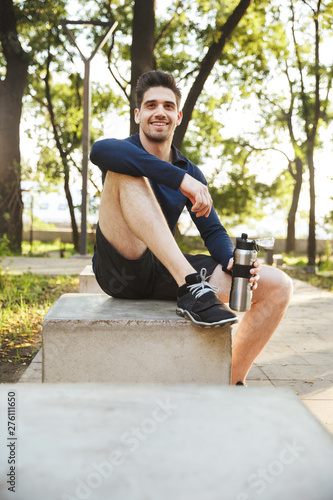 Poster Ouest sauvage Portrait of young athletic man sitting on bench and holding water bottle while doing workout in sunny green park