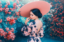 Cute Woman With Perfect Gentle Hairdo From Long Black Hair Wearing Pink Hat With Wide Brim, Elegant Look For Date And Photo Shoot, Lady With Open Back And Bright Lips, Girl In Blooming Roses