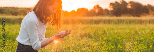 Teenager Girl closed her eyes, praying in a field during beautiful sunset Fototapeta