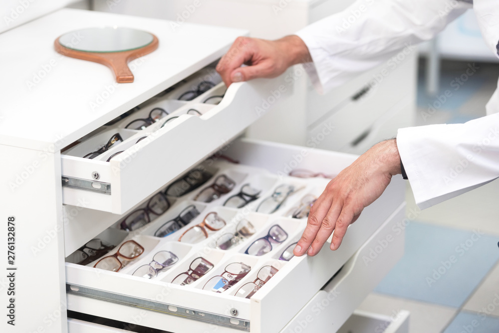 Fototapety, obrazy:  ophthalmologist hands close up, choosing glasses from a drawer in the optical store .