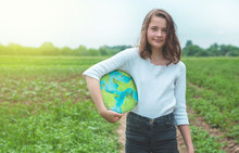Teen Girl Holding Planet In Hands Against Green Spring Background. Earth Day Holiday Concept. Protection And Love Of Earth