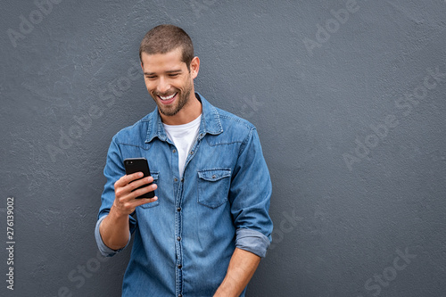 Cool smiling man using smartphone on grey wall Fototapete
