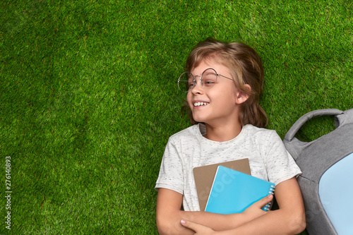 Fotografie, Obraz  Smiling schoolboy lying on grass and looking away