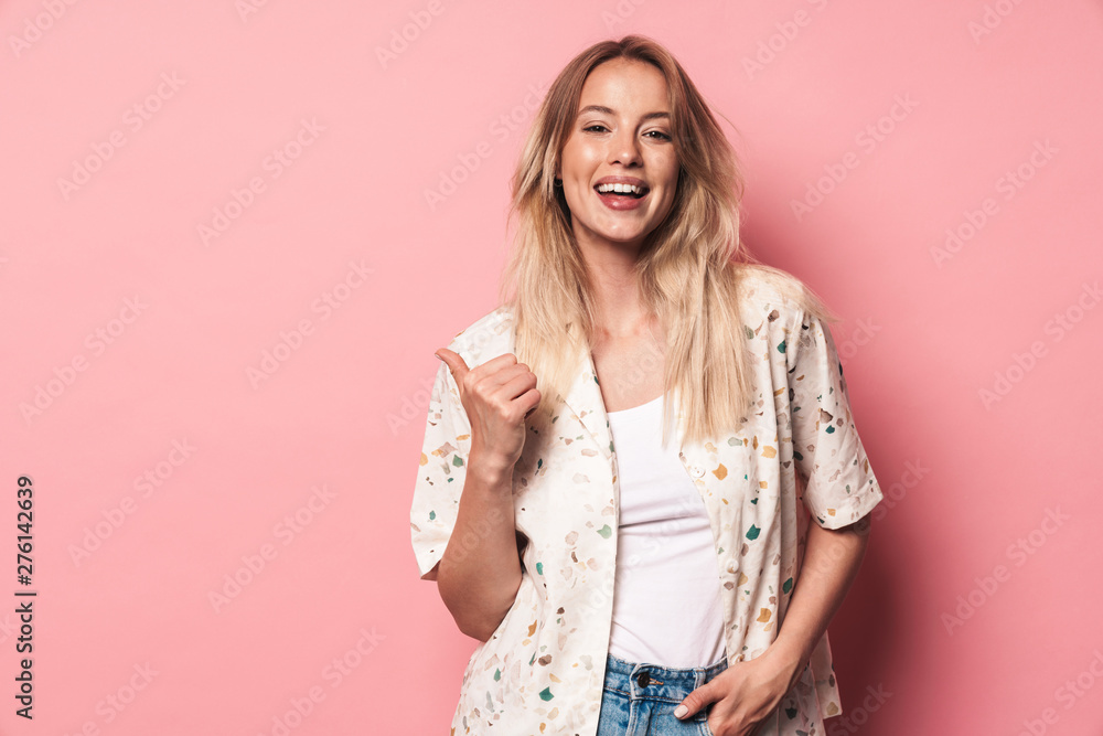 Beautiful smiling blonde woman posing isolated over pink wall background.