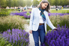 Outdoor Shot Of Happt Senior Female Wearing Blue Jeans, White Jacket And Silk Scarf Enjoying Amazing Violet Flowers In Bloom, Looking At Plants With Joyful Smile, Feeling Relaxed And Happy