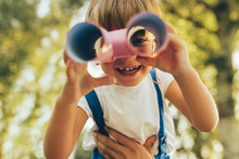Closeup Image Of Cute Little Boy Playing With A Binoculars Searching For An Imagination Or Exploration In Summer Day In Park. Happy Child Playing Pretend Safari Game Outdoors In The Forest. Childhood