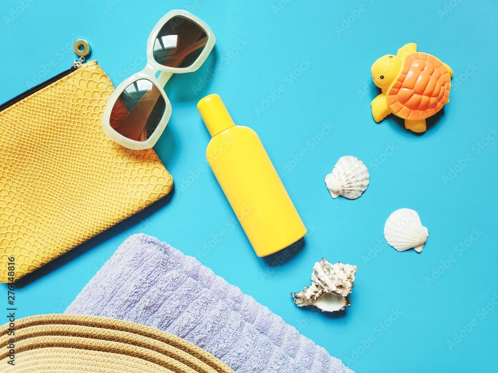 Fototapety, obrazy: Sunny flat lay beach photo. Yellow cosmetic bag, sunglasses, sunscreen, seashells, towel and rubber toy turtle on a blue background. Summer holidays with kids