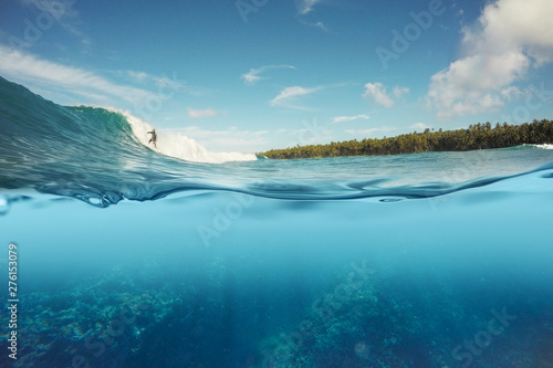 half underwater shot of surfer surfing a wave Canvas