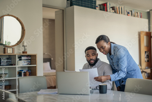 Young African American couple doing their online banking at home Poster Mural XXL