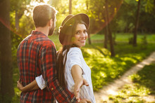 Positive Young Loving Couple Walking Outdoors In A Green Nature Park Forest.
