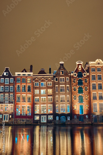 Brick houses and canal in amsterdam at night