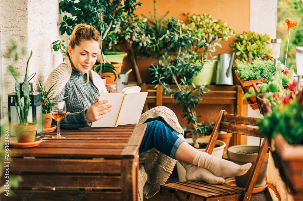 Fototapeta Young beautiful woman relaxing on cozy balcony, reading a book, wearing warm knitted pullover, glass of wine on wooden table