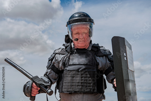 Photo  elderly man, war veteran trying on uniforms for special units in arms shop