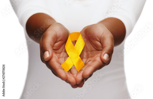 Fototapeta healthcare, charity and medicine concept - close up of woman cupped hands holding yellow gold childhood cancer awareness ribbon obraz