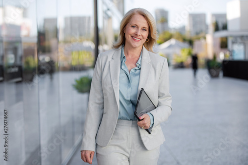 Fotografie, Tablou Cheerful middle aged 50's 60's corporate executive CEO in bright suit walking to