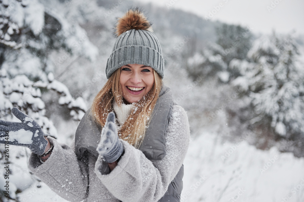 Fototapety, obrazy: Conception of winter holidays. Cheerful girl in warm clothes playing with snow outdoors near the beautiful forest