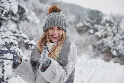 Conception of winter holidays. Cheerful girl in warm clothes playing with snow outdoors near the beautiful forest