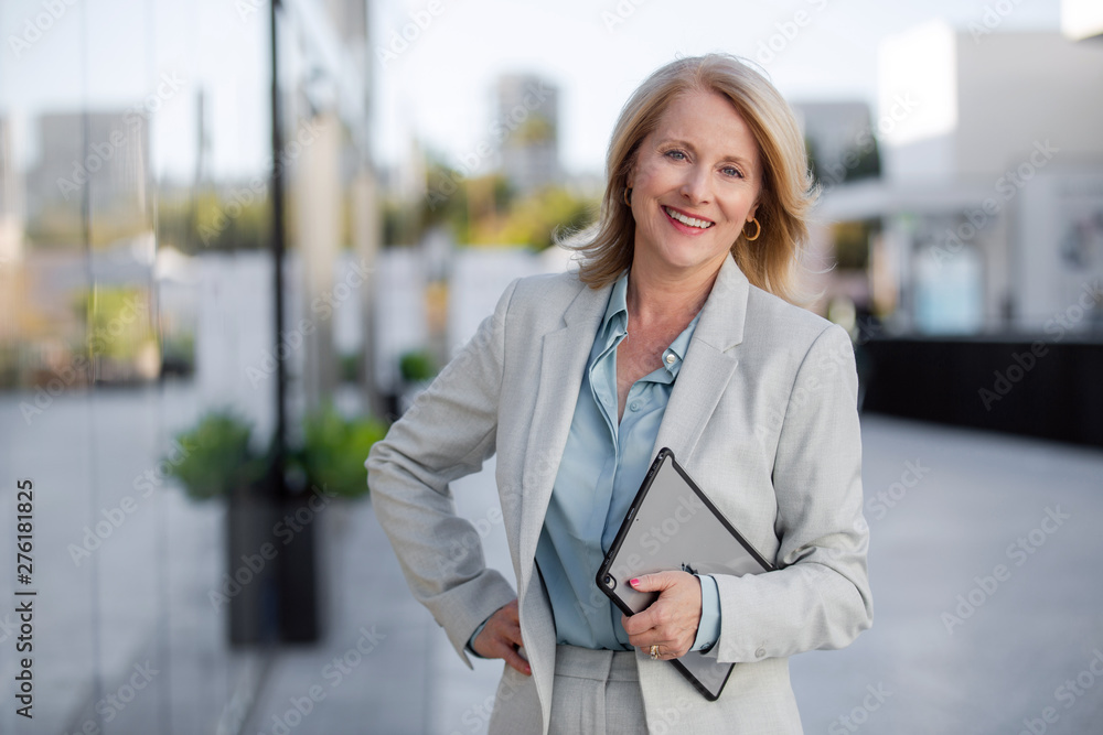 Fototapeta Mature business executive professional woman portrait, in suit outside of office in business district
