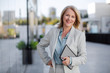 Leinwandbild Motiv Mature business executive professional woman portrait, in suit outside of office in business district