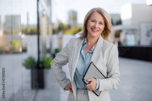 Obraz Mature business executive professional woman portrait, in suit outside of office in business district - fototapety do salonu