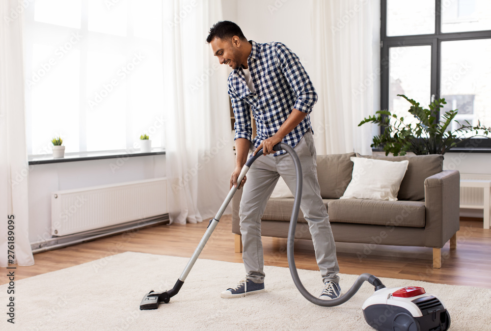 Fototapety, obrazy: household and cleaning concept - indian man with vacuum cleaner at home